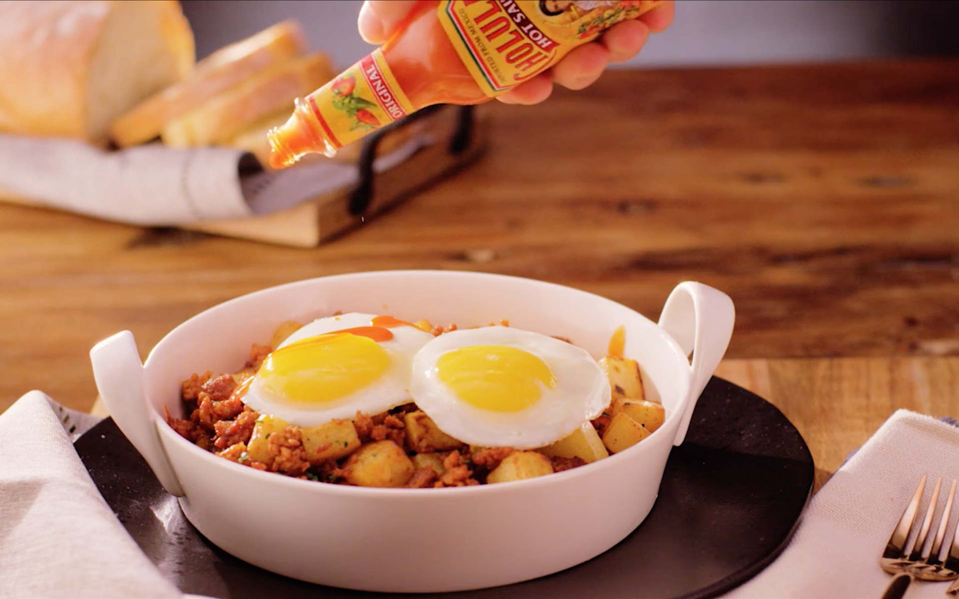 Adding Cholula Hot Sauce to a roasted potatoes & fried eggs meal - Fuse